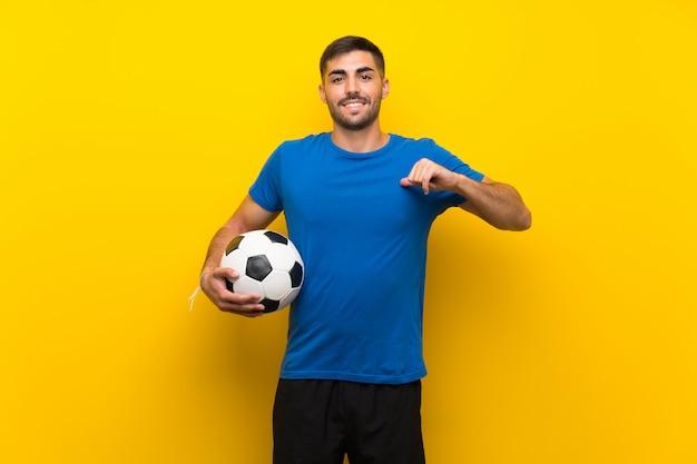 Молодой красивый футболист человек над изолированной желтой стеной гордый и самодовольный