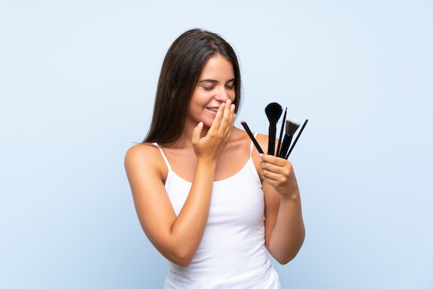 多くの笑みを浮かべて化粧ブラシの多くを保持している若い女の子