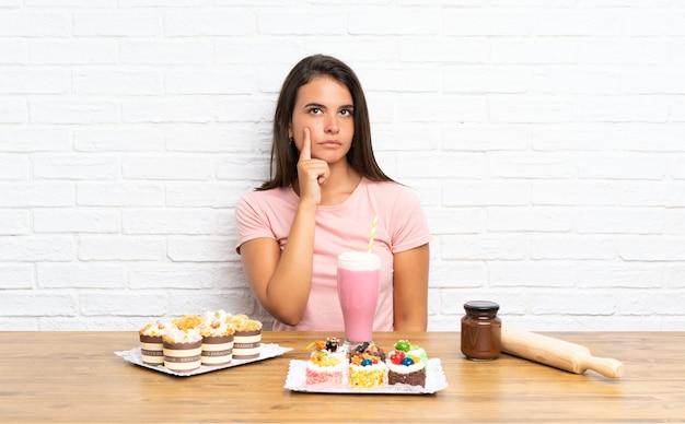 たくさんのアイデアを考えてさまざまなミニケーキを持つ少女