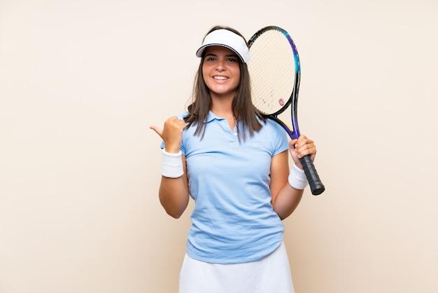 Молодая женщина играет в теннис над изолированной стеной, указывая в сторону, чтобы представить продукт