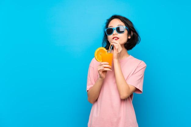カクテルを保持分離の青い壁の上のアジアの若い女性