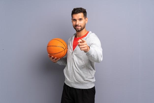 ハンサムな若いバスケットボール選手の男は自信を持って表情であなたに指を指す