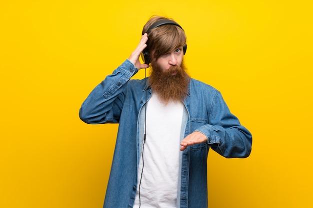 ヘッドフォンで音楽を聞いて孤立した黄色の壁に長いひげを持つ赤毛の男