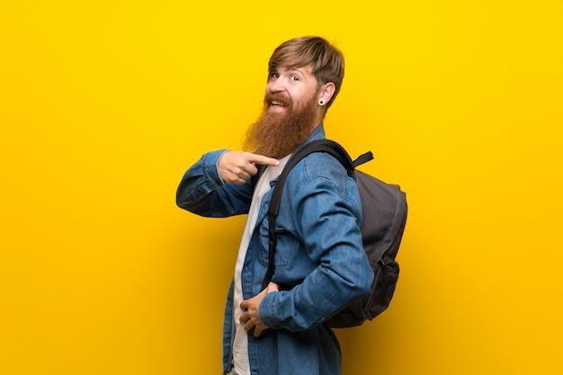 バックパックで孤立した黄色の壁に長いひげを持つ赤毛の男