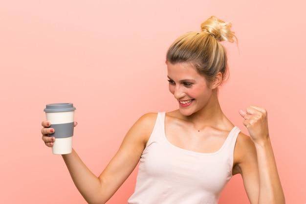 勝利を祝うテイクアウェイコーヒーを保持している若いブロンドの女性