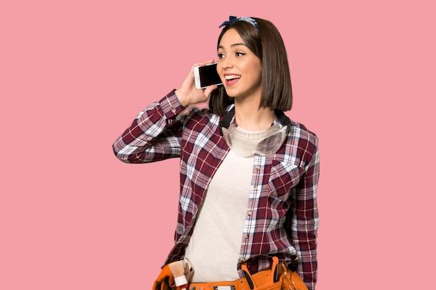 Женщина молодого работника держа беседу с мобильным телефоном на изолированной розовой стене