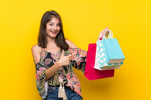 多くの買い物袋を保持している孤立した黄色の壁の上のカラフルなドレスの白人少女