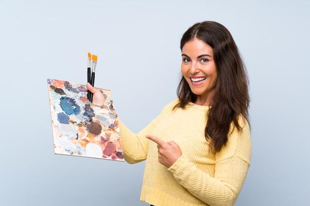 孤立した青い壁とそれを指している若いアーティストの女性