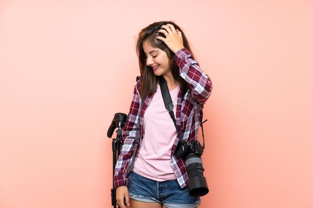 笑って孤立したピンクの壁の上の若い写真家の女の子