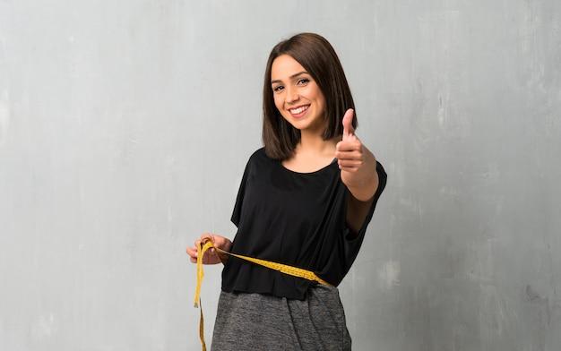 巻尺を持つ若いスポーツ女性