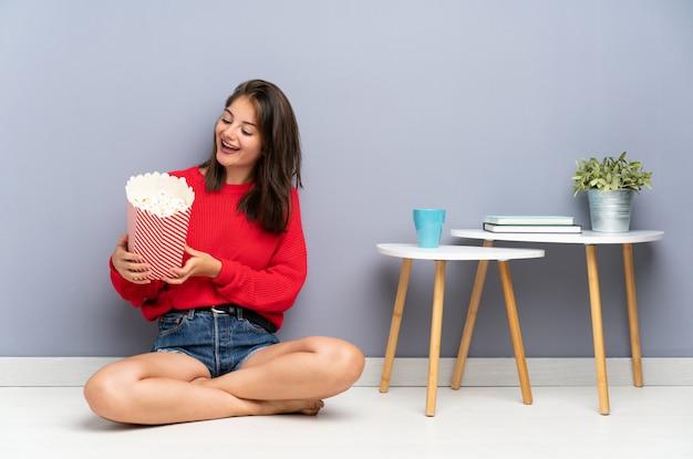 床に座ってポップコーンを保持している若い女性