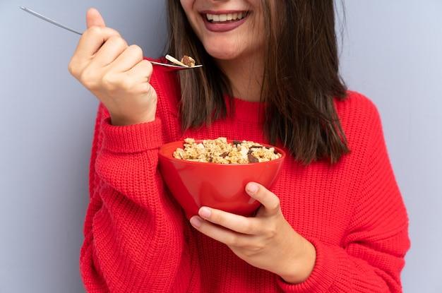 床に座って、穀物のボウルを保持している若い女性