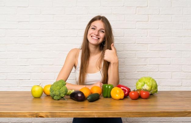 ジェスチャー親指を与える多くの野菜を持つ若い女性