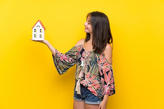 小さな家を保持している孤立した黄色の壁の上のカラフルなドレスの白人少女
