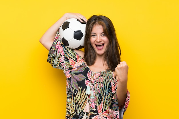 サッカーボールを保持している孤立した黄色の壁の上のカラフルなドレスの白人少女