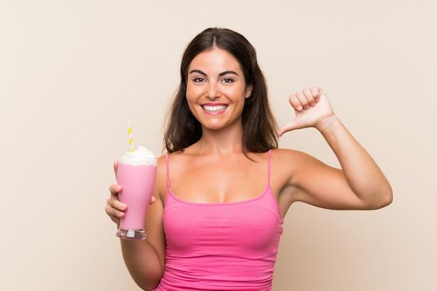 Молодая женщина с клубничным молочным коктейлем гордится и самодовольна