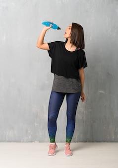 水のボトルを持つ若いスポーツ女性