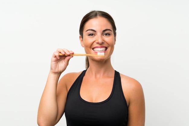 彼女の歯を磨く孤立した白い壁の上の若い女性