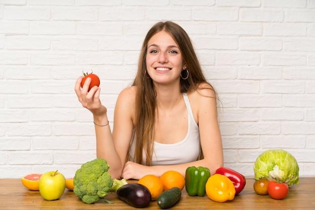 トマトを保持している若い女性