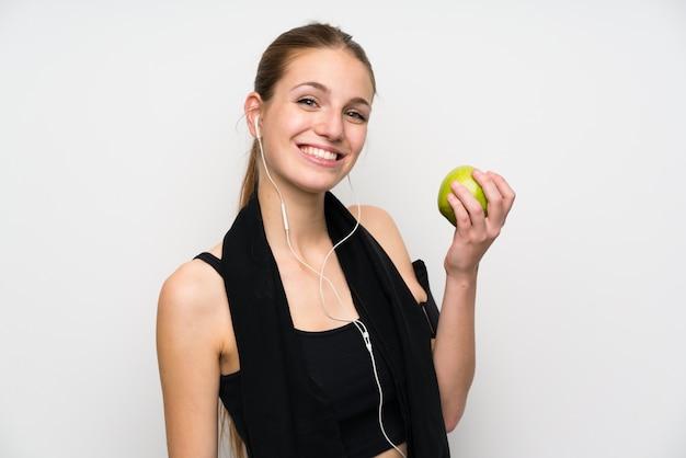 リンゴと分離の白い壁の上の若いスポーツ女性