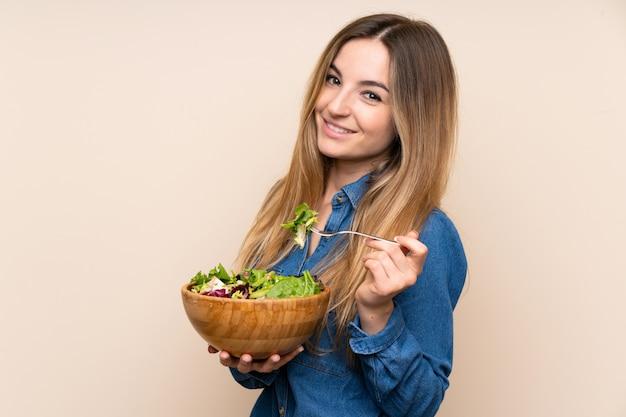 孤立した壁の上のサラダを持つ若い女性