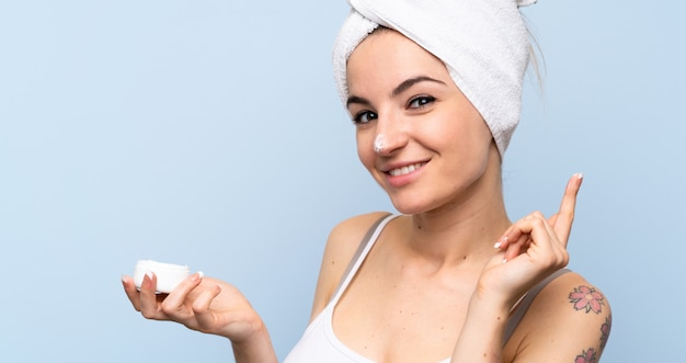 保湿剤と分離の青い壁の上の若い女性