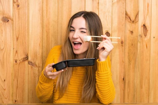 木製の背景の上に寿司を持つ若い女