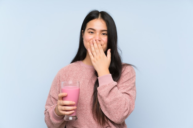 Молодой подросток азиатская девушка с клубничным молочным коктейлем с удивленным выражением лица