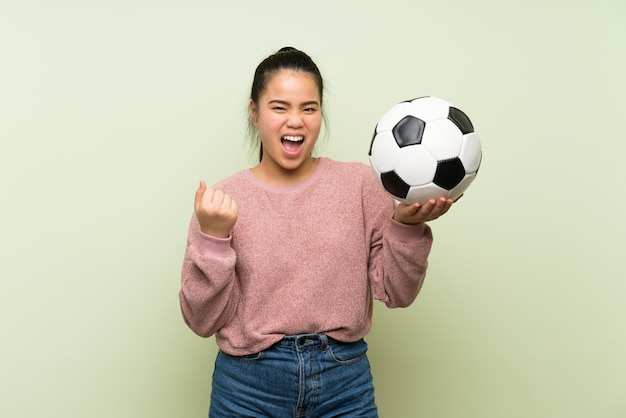Девушка молодого подростка азиатская над изолированной зеленой предпосылкой держа футбольный мяч