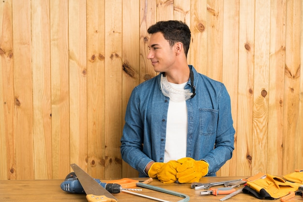 側にいる木製の背景上の職人男