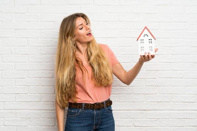 小さな家を保持している白いレンガの壁の上の若いブロンドの女性