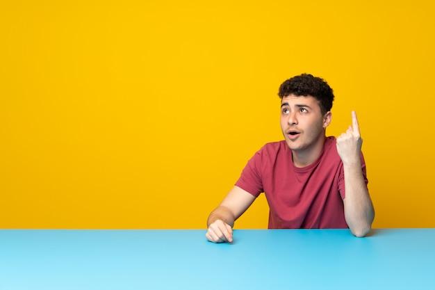 カラフルな壁とテーブルの上向きと驚いたと若い男