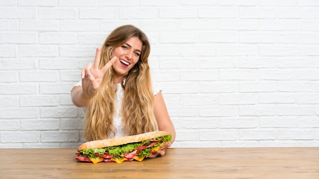 Молодая блондинка держит большой бутерброд, делая жест победы
