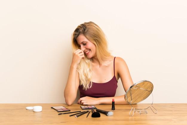 笑っているテーブルの化粧品で若いブロンドの女性