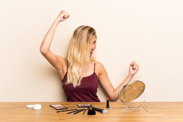 勝利を祝ってテーブルに化粧品で若いブロンドの女性