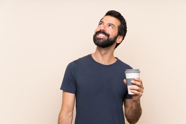 Человек с бородой, держа кофе, глядя вверх, улыбаясь