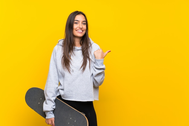 製品を提示する側を指している孤立した黄色の壁の上の若いスケーター女性