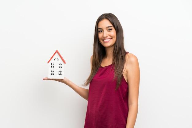 小さな家を保持している孤立した白い壁の上の若い女性