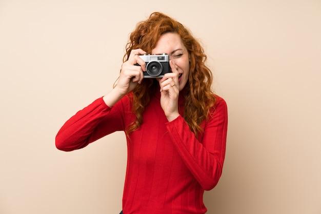 カメラを保持しているタートルネックのセーターと赤毛の女性