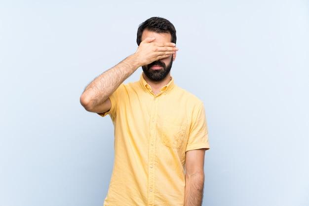 手で目を覆っている孤立した青い壁の上のひげを持つ若者。何かを見たくない