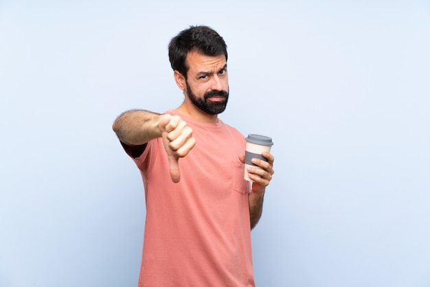負の表現と親指を示す分離の青い壁にテイクアウトコーヒーを保持しているひげを持つ若者