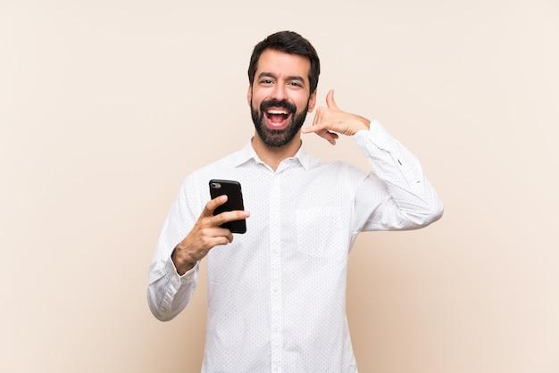 Молодой человек с бородой, держа мобильный телефон делает жест. перезвони мне знак