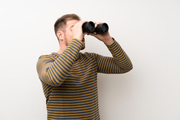 黒の双眼鏡で孤立した白い壁の上のハンサムな男