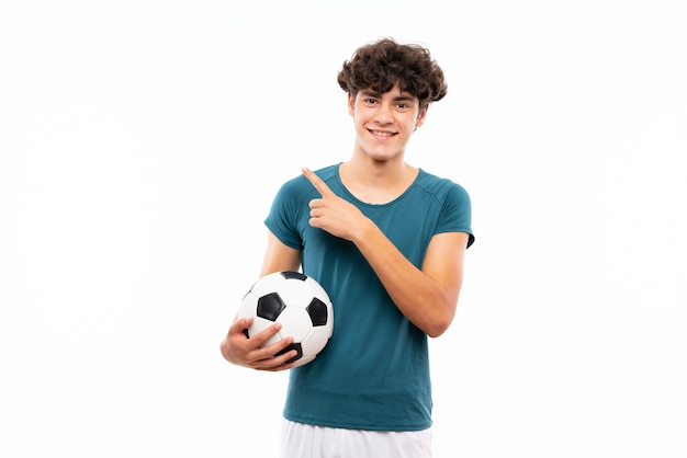 製品を提示する側を指している孤立した白い壁の上の若いフットボール選手男