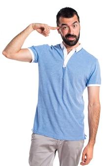 狂ったジェスチャーを作る青いシャツを持つ男