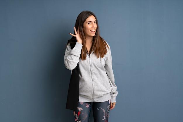 耳に手を置くことで何かを聞いて若いスポーツ女性
