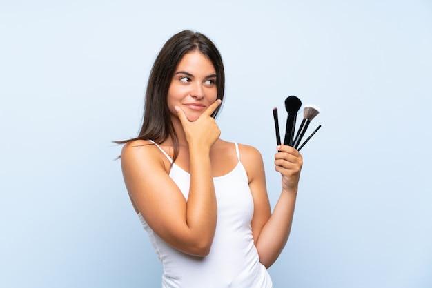アイデアを考えて化粧ブラシの多くを保持している若い女の子