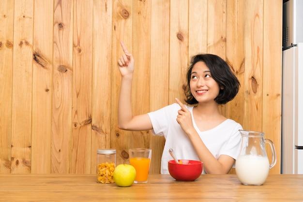 人差し指で素晴らしい朝食を指している朝食ミルクを持つアジアの若い女性