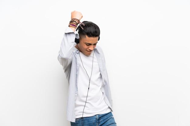 イヤホンで孤立した白い壁の上の若い男