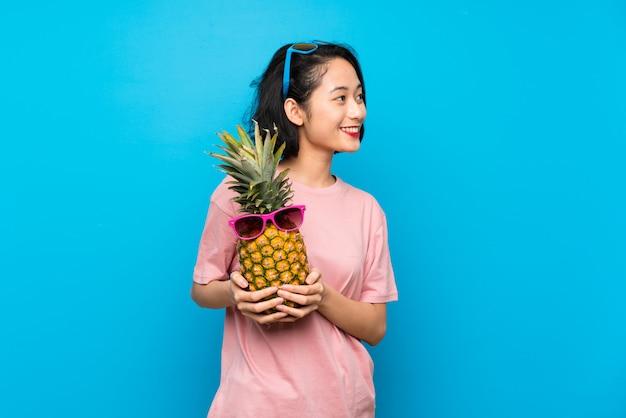 サングラスとパイナップルを保持している分離の青い壁の上のアジアの若い女性